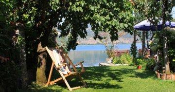 Es ist eine Liege zum Entspannen zu sehen, im Schatten von einem Baum im Garten